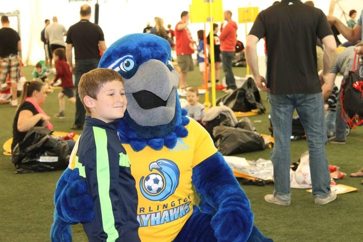Burli hugs a child, burlington Bayhawks custom mascot costume
