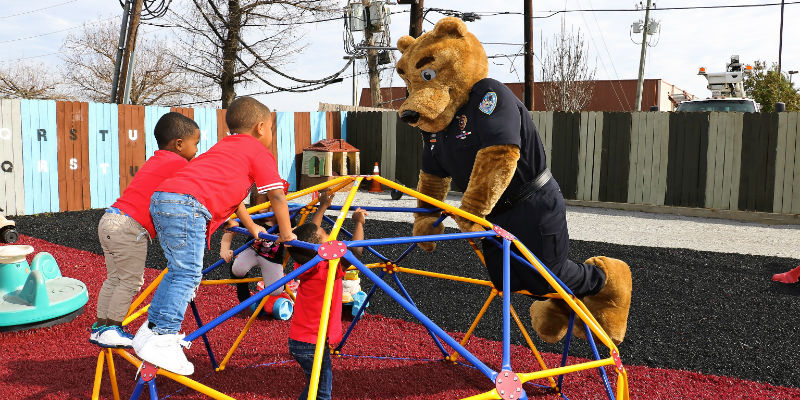 Barran's Bear mascot playing on climbing frame with children