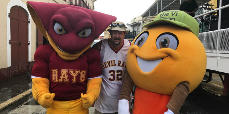Two sports mascots with a fan