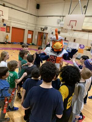 Rugby United New York Rooster with a group of children