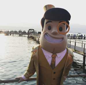 The Capitalist mascot standing next to a lake